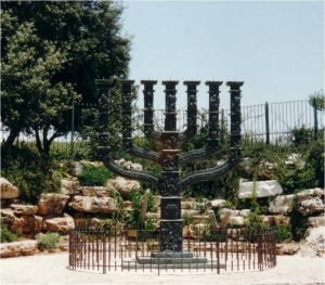 """The Knesset Menorah, situated on the edge of the Rose Garden across from the Knesset building, is the work of the Jewish-English artist of German origin Benno Elkan (1877 – 1960). The Menorah is molded of bronze and resembles the menorah (7-branched candelabra) of the Temple, which has come to be a Jewish symbol. The sculpture is 4.30 meters high, 3.5 meters wide, and weighs 4 tons. The main theme of the work depicts the spiritual struggles of the Jewish people and it is engraved with the passage """"Not by strength and not by power, but by my Spirit, says the Lord who rules over all"""" (Zechariah 4, 6). The Menorah includes engravings of biblical figures and events from the tradition and history of the Jewish people. The engravings on the six side branches of the Menorah portray the fate of the Israeli people since it was exiled from its land, and the engravings on the center branch portray the people's fate since the beginning of the return to the land up to the establishment of the State of Israel."""