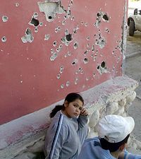Israeli girl next to a house damaged in a missile attack