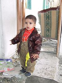 Palestinian boy in a house damaged during the Gaza War