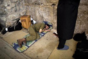 Soldier sleeping at the Wall during all night study and prayer.
