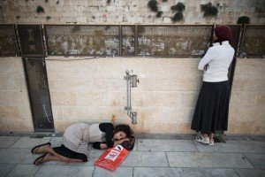A woman sleeps at the Wall during Tish b'Av all night study and prayer.